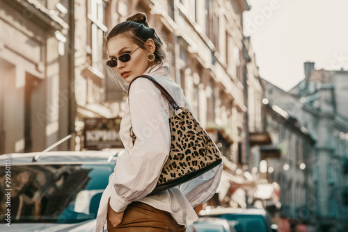 Outdoor autumn fashion portrait of elegant, luxury woman wearing sunglasses, trendy white shirt, leather trousers, with animal, leopard print bag, walking in street of European city. Copy, empty space