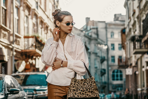Outdoor autumn fashion portrait of elegant, luxury lady wearing sunglasses, trendy white shirt, wrist watch, holding animal, leopard print bag, posing in street of European city Poster Mural XXL