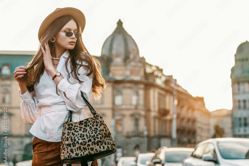 Fototapeta Outdoor fashion portrait of elegant, luxury woman wearing beige hat, sunglasses, trendy white shirt, brown wrist watch, holding animal, leopard print bag, posing in street. Copy, empty space for text