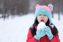 Portrait Of Asian Teen Girl Holding A Snowball In Hands