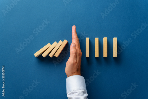 Poster Individuel View from above of male hand interfering collapsing dominos