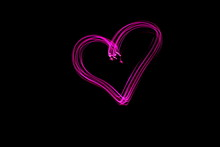 Long Exposure Photograph Of A Heart Shape Outline In Pink Neon Colour In An Abstract Swirl, Parallel Lines Pattern Against A Black Background. Light Painting Photography.