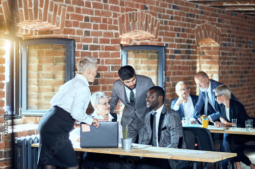 Photographie  In the foreground two blonde caucasian women, caucasian bearded brunette man, african man talk