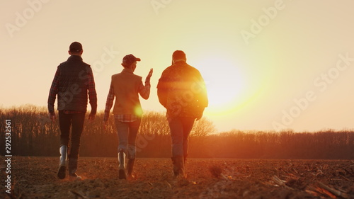 Foto Three farmers go ahead on a plowed field at sunset