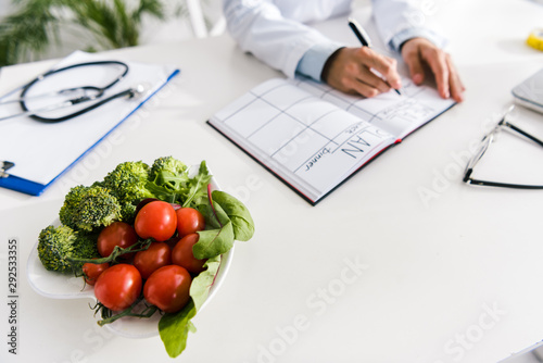 Photo  cropped view of nutritionist writing in notebook with meal plan near vegetables