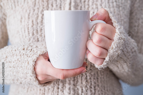 Girl in a warm cardigan is holding white mug