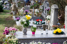 Marble Tombstone In A European Cemetery - Full Of Flowers And Lamps With Candle - All Souls Day Decoration And Remembrance