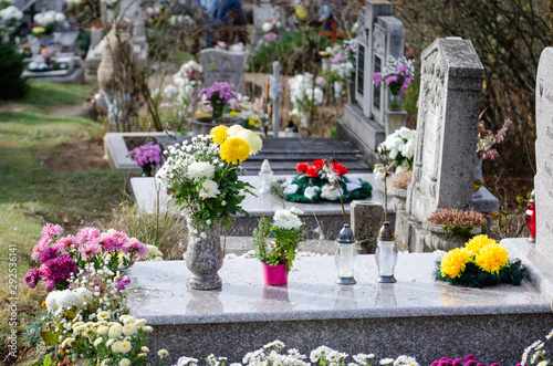 Marble tombstone in a European cemetery - full of flowers and lamps with candle Canvas Print