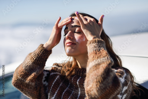 Young woman applying sunscreen on her face in snow landscape