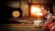 Leinwandbild Motiv Fireplace and slim woman legs with christmas socks