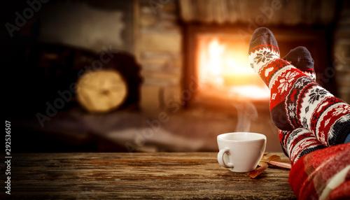 Fotografija Fireplace and slim woman legs with christmas socks