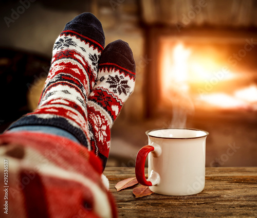 Fireplace and slim woman legs with christmas socks