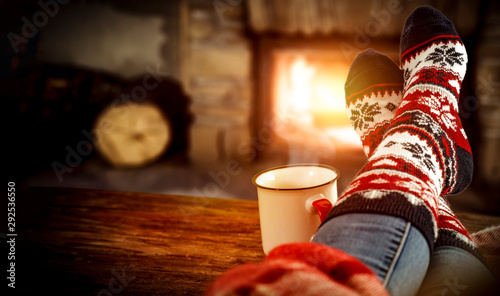 Fotomural Fireplace and slim woman legs with christmas socks