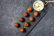 fresh vegetarian falafel balls with sauce on black stone background