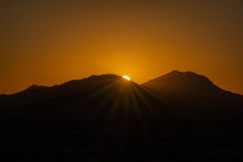 Sun Peaking Over Mountains At Sunrise In The Mojave Desert
