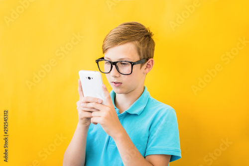 Pinturas sobre lienzo  Handsome boy in glasses plays tablet