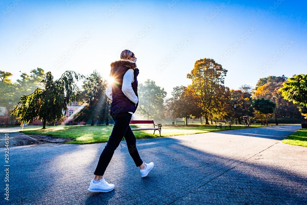 Fototapeta Middle-aged woman walking in city park