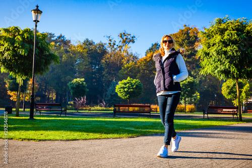 Obraz Middle-aged woman walking in city park - fototapety do salonu