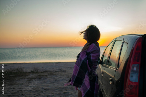 Fotografia, Obraz  Woman in a plaid with windswept hair standing near the Sea coast at sunset