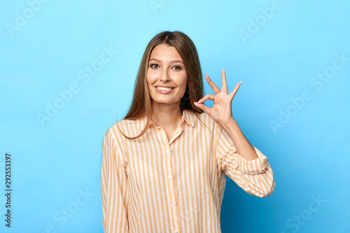 cheerful young beautiful woman in stylish striped shirt shows ok sign with hand as expresses approval, expresses cheerful expression Canvas Print