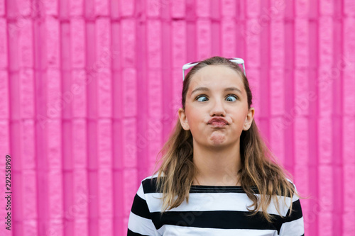 Cute caucasian girl making a funny face in front of a hot pink vibrant colored w Wallpaper Mural