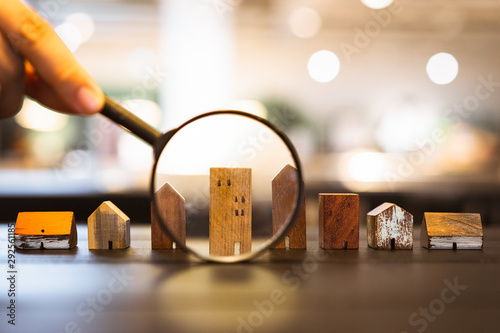 Cuadros en Lienzo  Hand holding magnifying glass and looking at house model, house selection, real estate concept