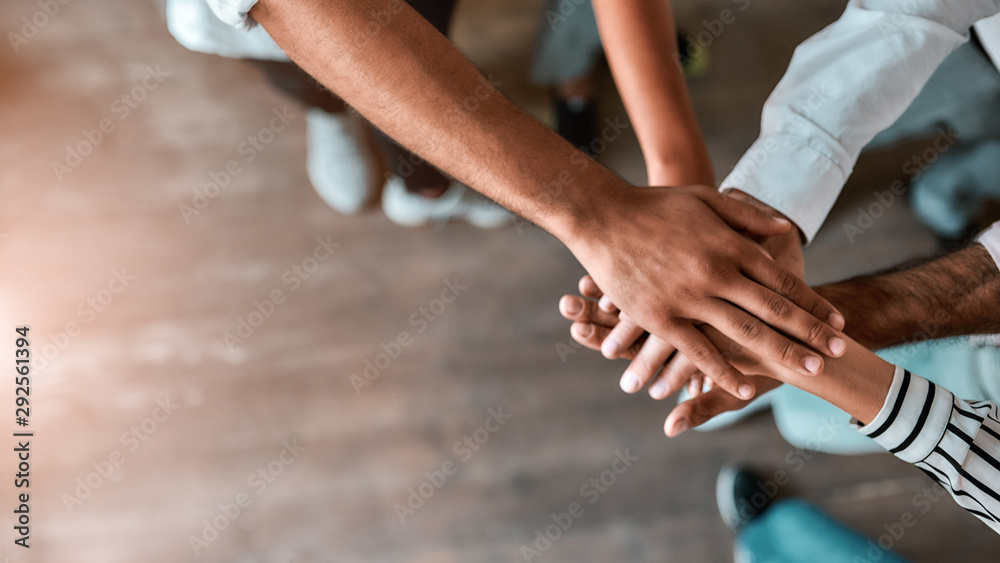 Fototapeta Successful team. Top view of business people holding hands together while standing in the office