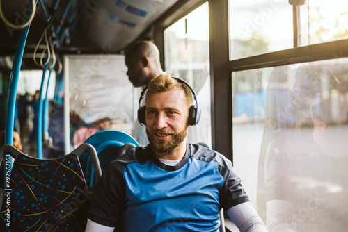 Young man in bus listening to music - 292562163