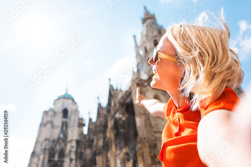 Vászonkép  A young woman in a bright orange dress stands on the background of St