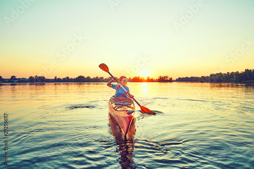 People kayak during sunset in the background Canvas-taulu