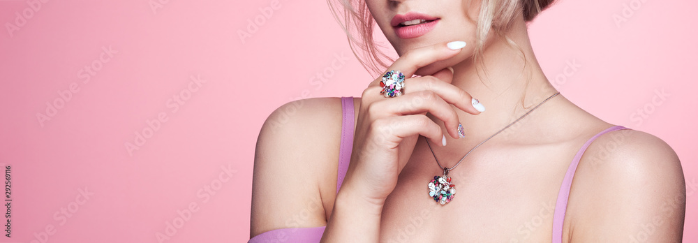 Fototapeta Beauty Woman with perfect Makeup and Manicure. Glamour Girl with Jewelry. Pink Lips and Nails. Precious Stones and Silver. Beauty girls Face isolated on light Background. Fashion photo