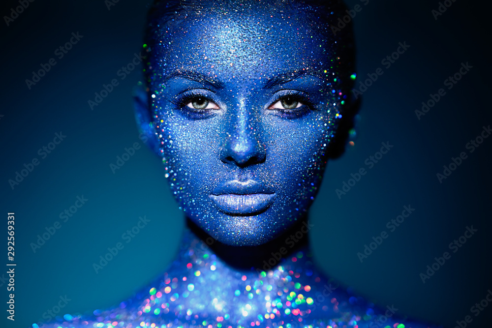 Fototapeta Fashion model woman in blue bright sparkles and neon lights posing in studio. Portrait of beautiful sexy woman. Art design colorful glitter glowing make up