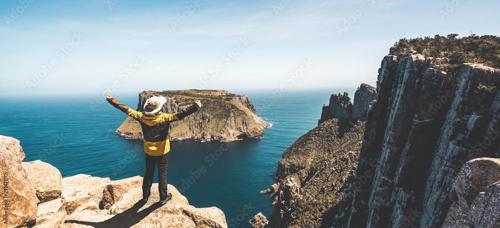 Fototapety, obrazy: Young man trekker hiking on beautiful coast cliff of Tasman National Park in Tasman peninsula, Three Capes Track near Port Arthur in Tasmania, Australia.