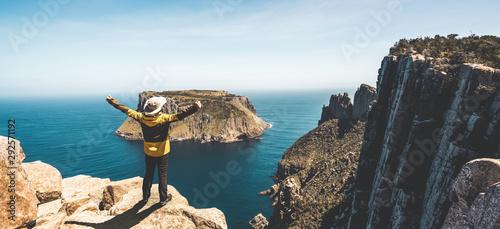 Young man trekker hiking on beautiful coast cliff of Tasman National Park in Tasman peninsula, Three Capes Track near Port Arthur in Tasmania, Australia Fotobehang