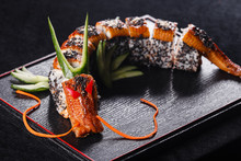 Sushi Dragon With Eel, Cucumber And Avocado On A Black Background. Japanese Food, Tasty Of Meal For Lunch