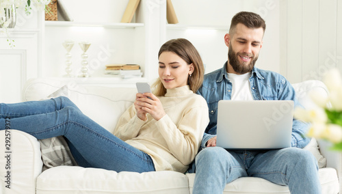 Couple at home. Man with laptop, woman with phone Fototapet