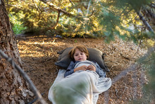 6 Year Old Boy Lying Down On Pine Needles Under Large Pine Tree.