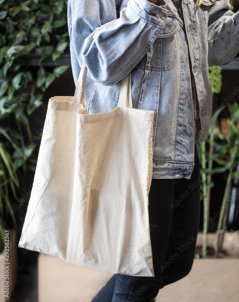Fototapety, obrazy: Girl dressed in denim jacket holding eco-bag