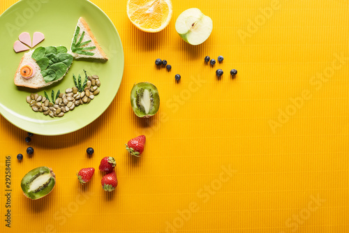 top view of plate with fancy fish made of food near scattered fruits on colorful orange background