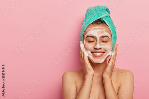 Pleased smiling woman washes face with cleansing gel, has soap on complexion, keeps eyes shut, wears wrapped towel on head, has naked body, poses against pink background, copy space on left Fototapete