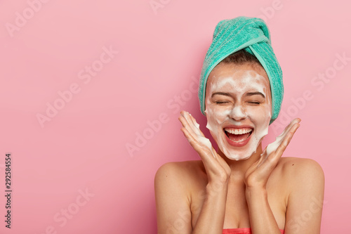Fototapeta Happy joyous young girl spreads palms over face, washes face with soap, has fun in bathroom, pampers skin, wears wrapped towel on head, expresses positive emotions, poses against pink background obraz