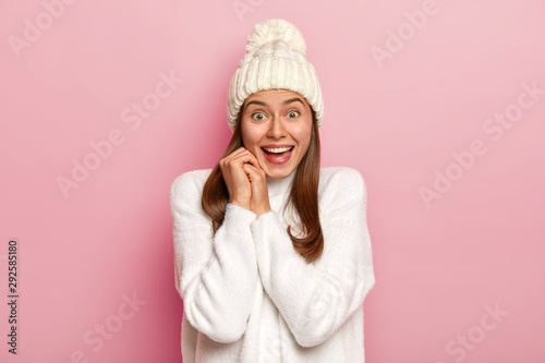 Fotografia, Obraz  Joyful dark haired millennial girl has happy reaction on good news, smiles broadly, wears warm winter hat and comfortable white sweater, has enthusiastic gaze, isolated on pink wall