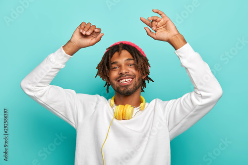 Horizontal view of optimistic relaxed Afro American man with dreads, enjoys beats while listning music or new track via headphones, keeps arms raised, has alluring smile, dressed in white sweater. - 292586397