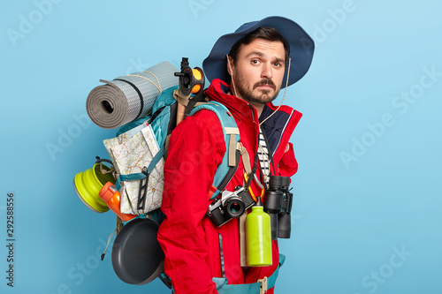 Fotomural Photo of active handsome man with mustache and bristle, carries tourist rucksack on back, walks in forest, has hiking trip, wears red jacket and hat, stands against blue background