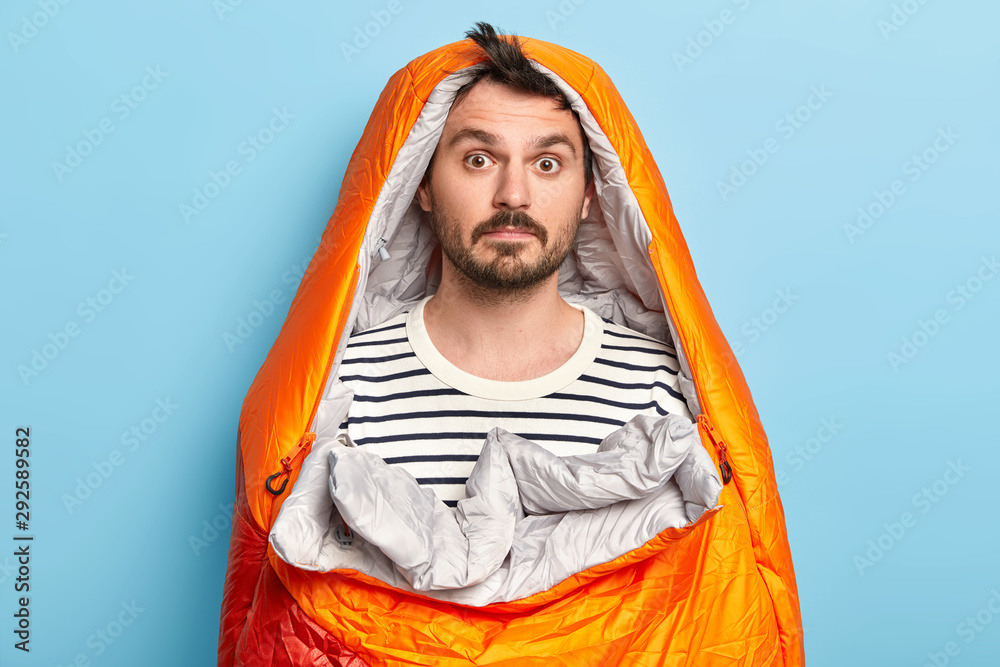 Fototapeta Photo of surprised bearded male camper poses in sleeping bag, wears striped jumper, spends weekend actively, poses over blue background, has expedition near rocky mountains. Active rest concept