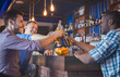 Happy Guys Clinking Beer Bottles In Bar