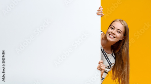 Beautiful teenage girl looking out of white blank placard Billede på lærred