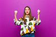 canvas print picture - young pretty woman celebrating an unbelievable success like a winner, looking excited and happy saying take that! against purple background