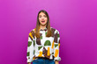 canvas print picture - young pretty woman feeling terrified and shocked, with mouth wide open in surprise against purple background