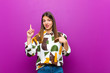 canvas print picture - young pretty woman feeling proud and surprised, pointing to self confidently, feeling like successful number one against purple background